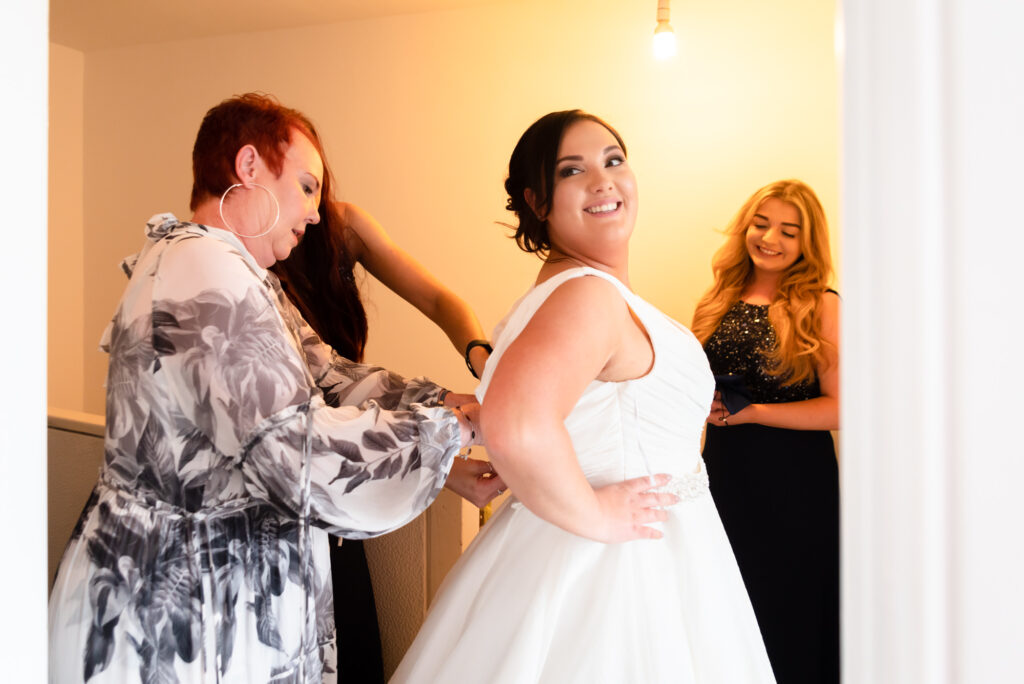 Bride getting fitting in her dress