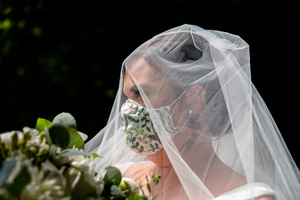 Bride wearing a mask and a veil at st paul's church compstall