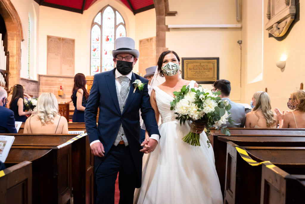 Bride and groom walking down the aisle with masks at st paul's church compstall