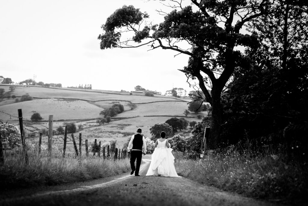 Bride and groom walking down the road at Thornsett Fields Farm