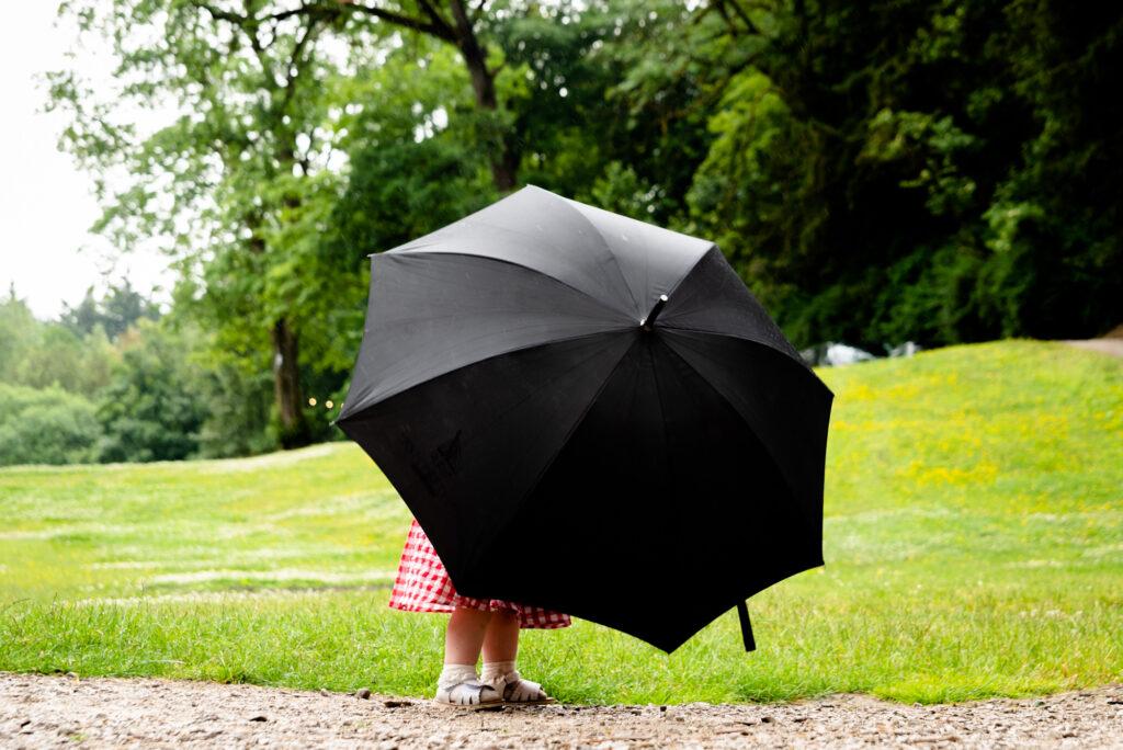 Little flower girl under a giant umbrella