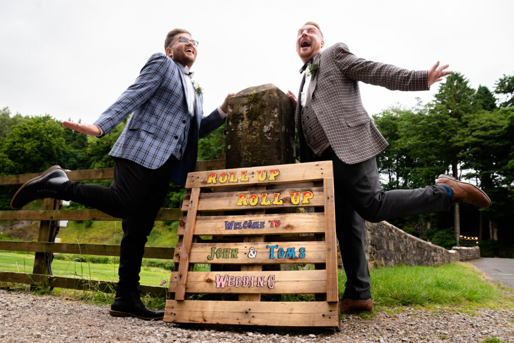Grooms posing in front of their wedding sign