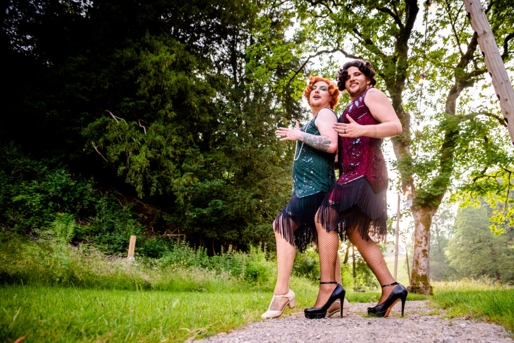Two grooms in 1920's drag having fun with their portrait session at Gisburne Park Estate