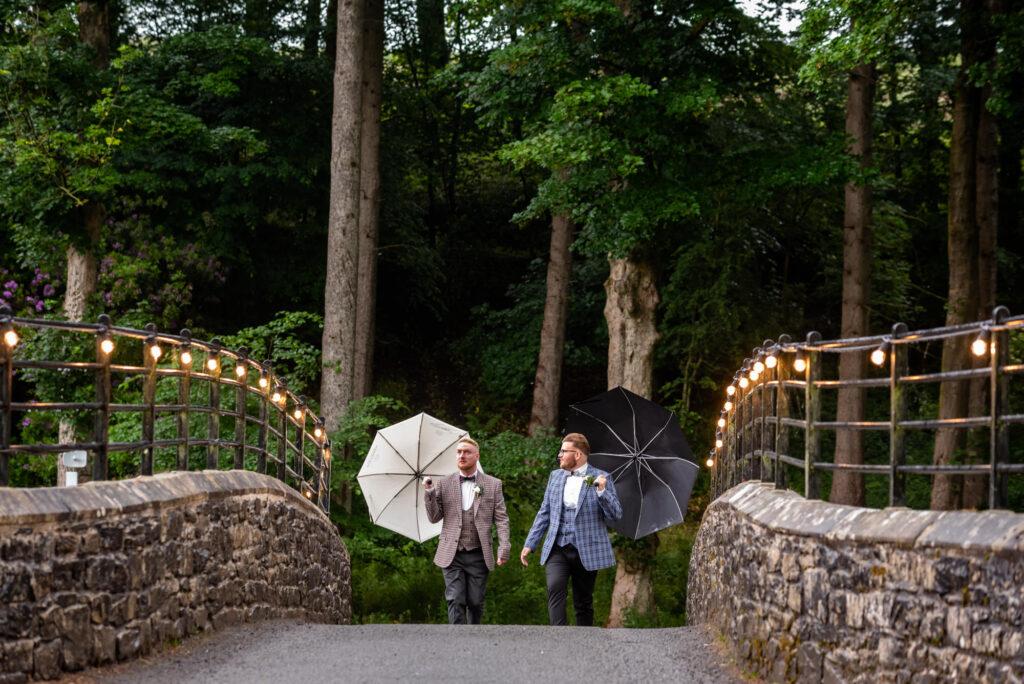 Grooms walking over the bridge towards the wedding site at Gisburn Park Estate