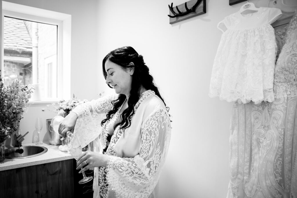 Bride pouring a glass of bubbly at Hanbury Wedding Barn
