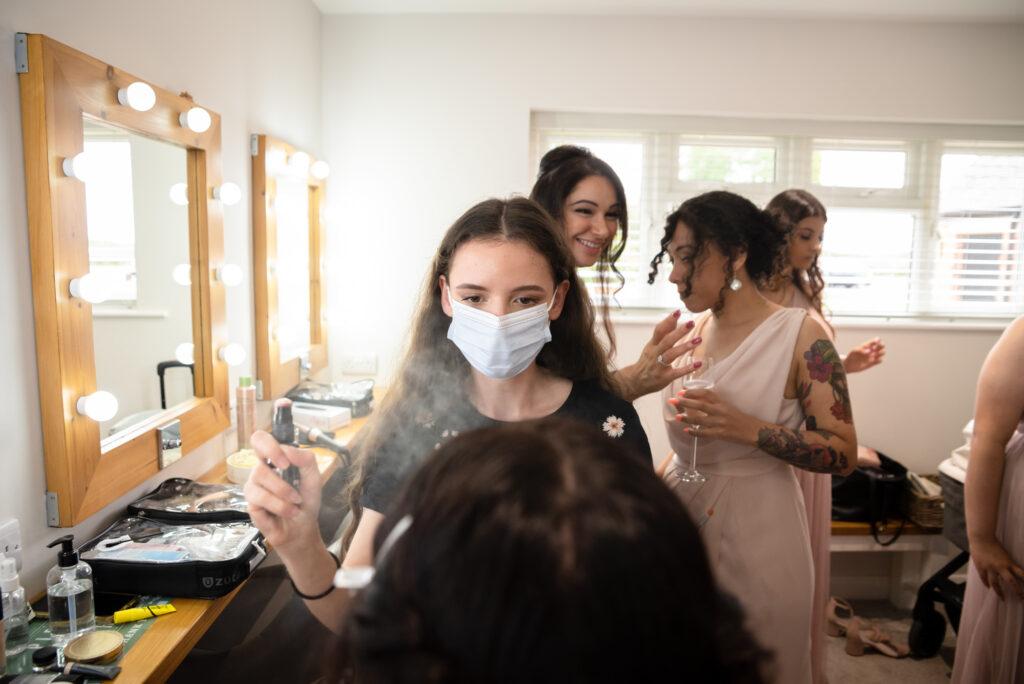 Make up artist spraying mist on the bride's face at Hanbury Wedding Barn