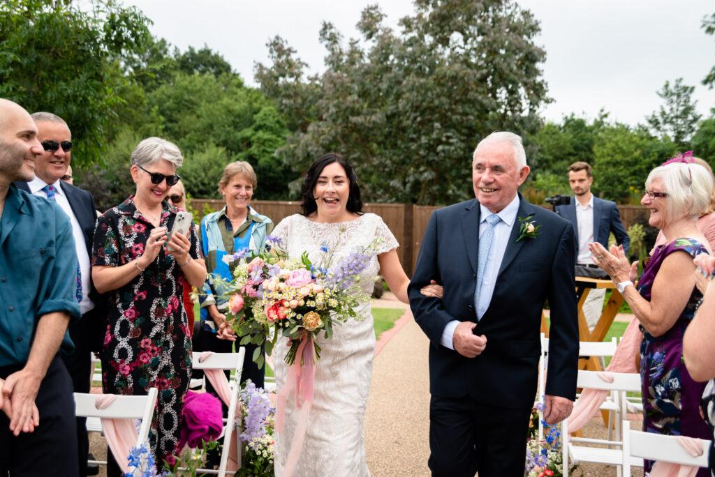 Bride walking down the aisle at Hanbury Wedding Barn