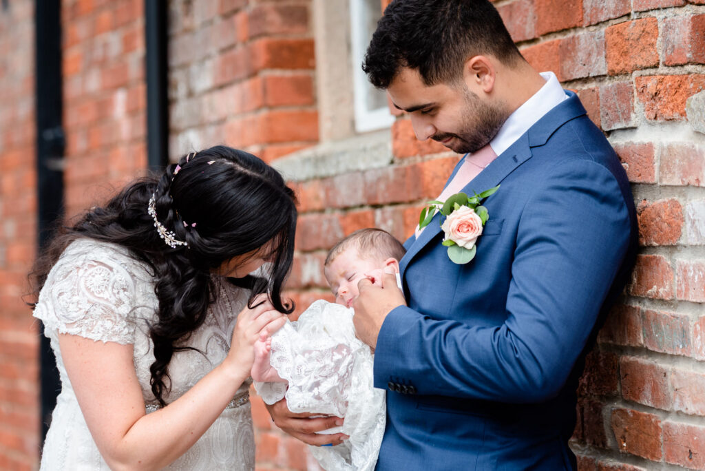 Bride and groom with their baby at Hanbury Wedding Barn