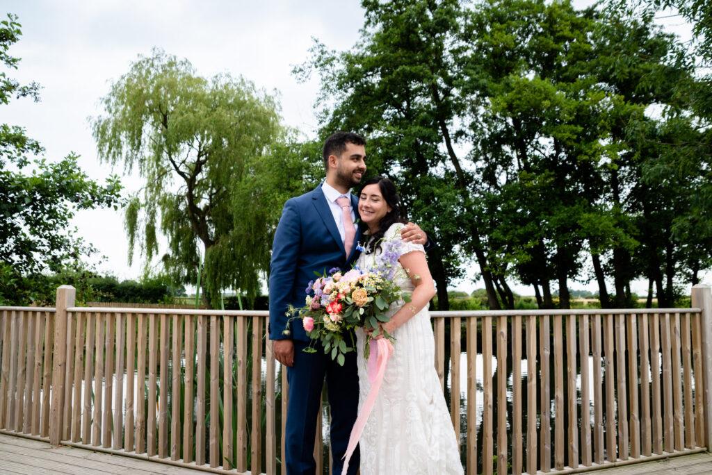 Bride and groom on the decking at Hanbury Wedding Barn