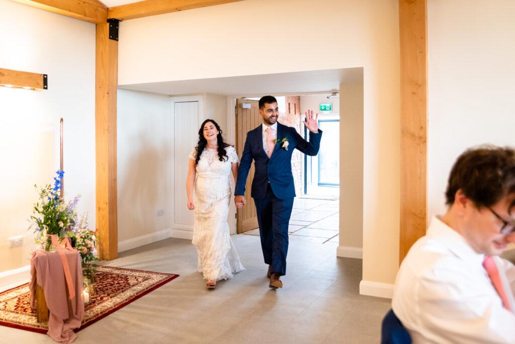 Bride and groom making an entrance at Hanbury Wedding Barn