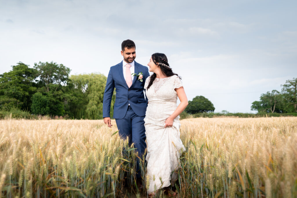 Bride and groom walking through the field