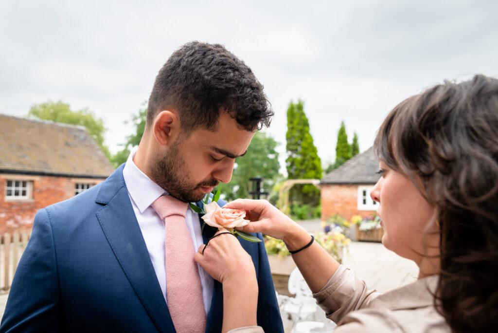 Florist fitting the buttonhole flower on the groom at Hanbury Wedding Barn