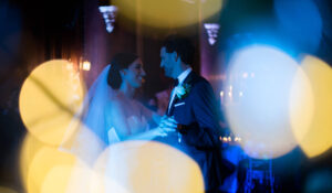 Bride and groom having a their first dance at Thornton Manor, photographed through the Christmas lights