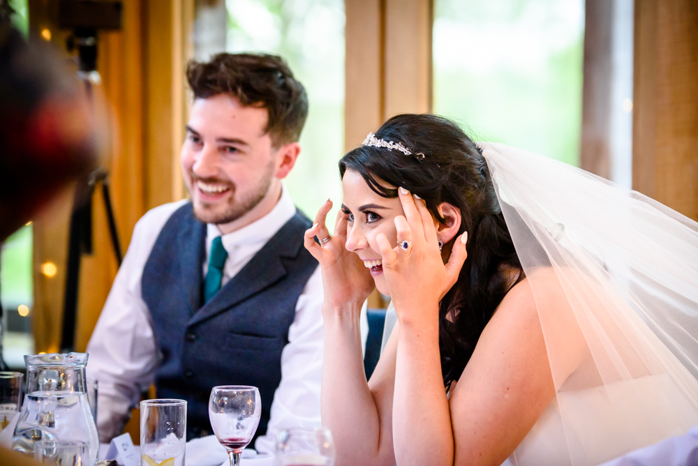 Bride and groom laughing during the speeches at Oak Tree of Peover