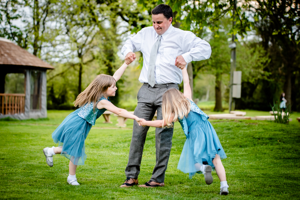 A guest spinning two children during the wedding reception at Oak Tree of Peover