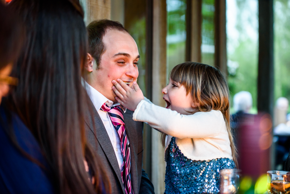 Little girl grabbing her father's face A guest spinning a child during the wedding reception at Oak Tree of Peover