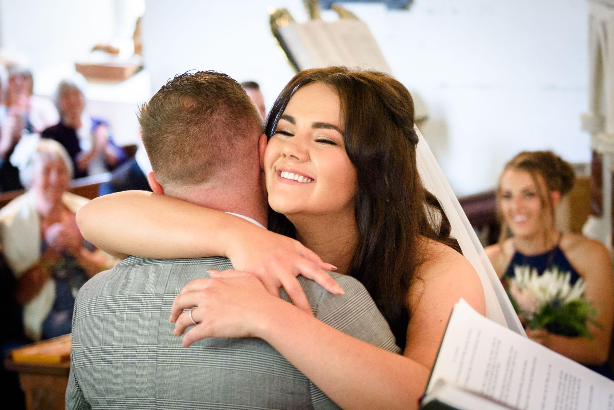 bride hugging groom at st mary's church in Llanfairpwllgwyngyll