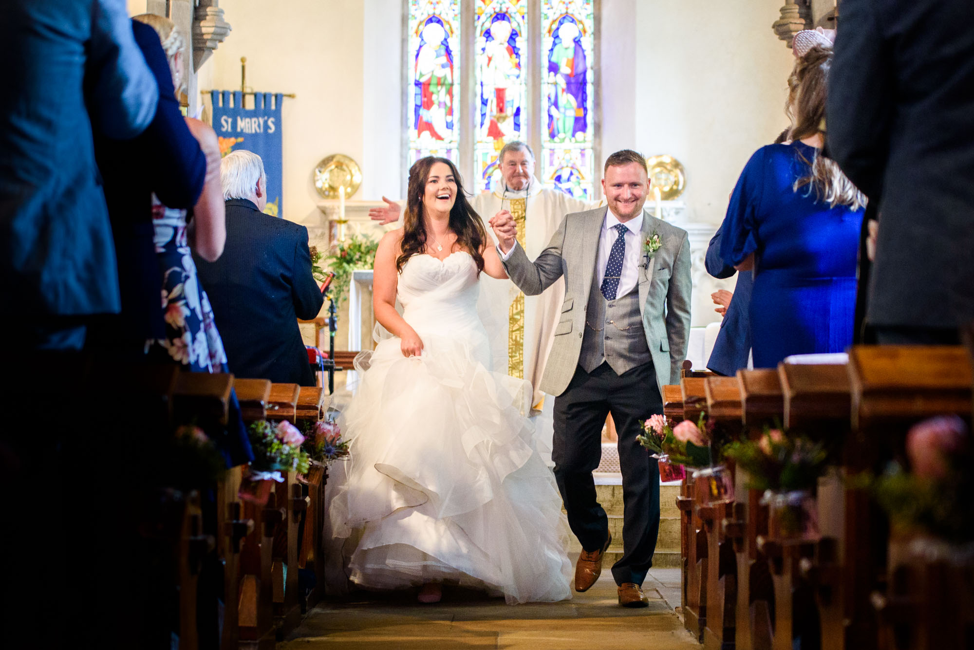 bride walking down the isle at st mary's church in Llanfairpwllgwyngyll