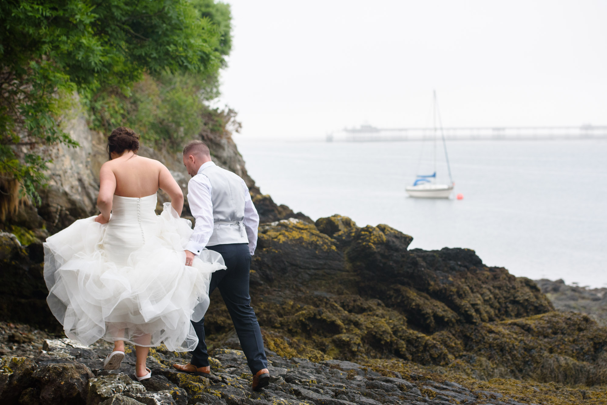 Bride and groom walking on the beach in Anglesey