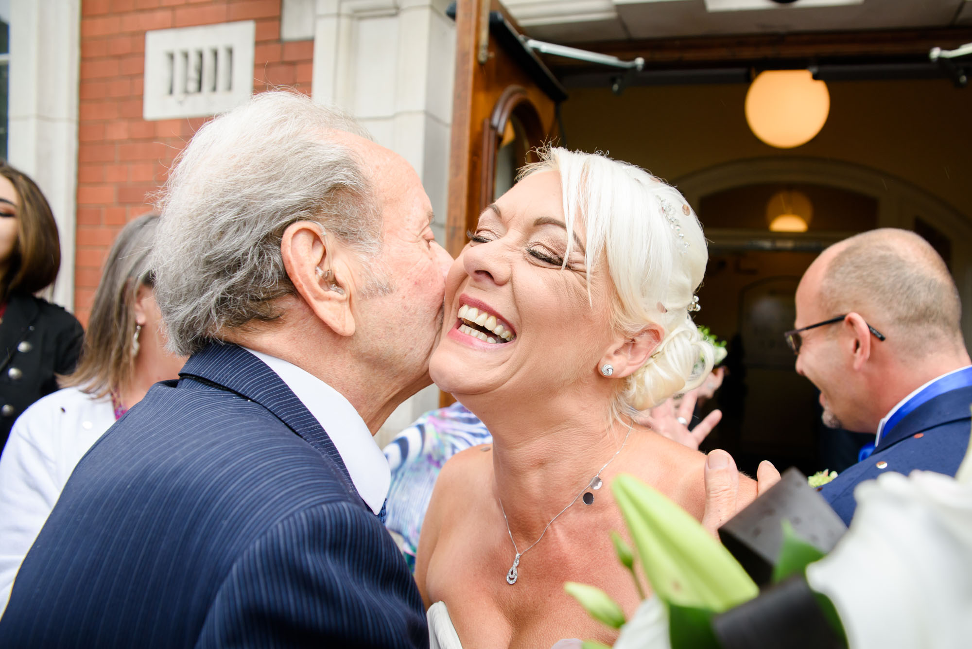 Bride kissing her father in law outside Stockport registry office