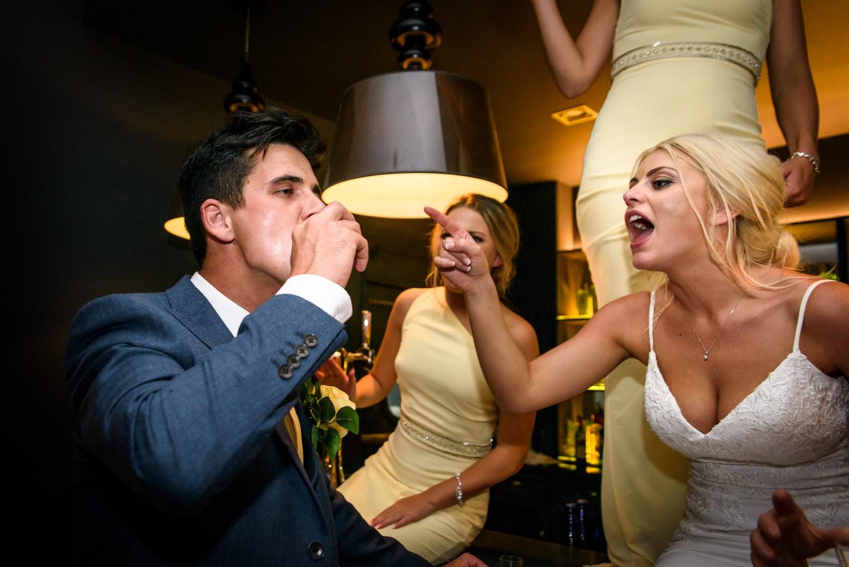 Bride encouraging the groom to drink